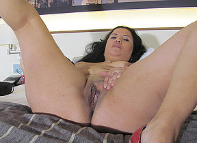 Kinky mature hussy playing on her bed with a dildo